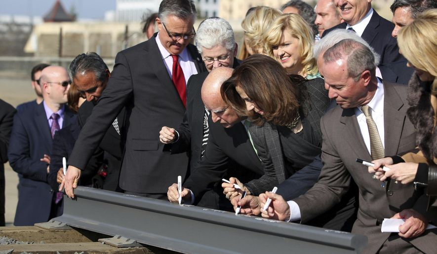 FILE - In this Jan. 6, 2015, file photo, Gov. Jerry Brown, center, and his wife, Anne Gust Brown, fourth from right, sign a portion of a rail at the California High-Speed Rail Authority groundbreaking event as Gina McCarthy, administrator of the U.S. Environmental Protection Agency, standing next to Brown at left, watches in Fresno, Calif. A bipartisan team of lawmakers are seeking a formal audit of California's high-speed rail project following a nearly $3 billion jump in costs. Democratic Sen. Jim Beall and Republican Assemblyman Jim Patterson will make their pitch for the audit Tuesday, Jan. 30, 2018, to a joint committee that will choose whether to authorize it. (AP Photo/Gary Kazanjian, File)