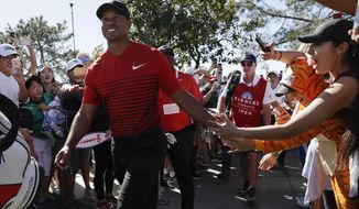 Tiger Woods greets fans as he makes his way to the seventh hole of the South Course at Torrey Pines Golf Course during the final round of the Farmers Insurance Open golf tournament, Sunday, Jan. 28, 2018, in San Diego. (AP Photo/Gregory Bull)