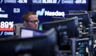 A Nasdaq employee works at the Nasdaq MarketSite, in New York, Tuesday, Jan. 30, 2018. Health care stocks are leading U.S. indexes broadly lower in early trading following news of a big new venture in the health care business. (AP Photo/Richard Drew)