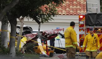 Police investigate the scene where several people were killed and others injured when a helicopter crashed into a home in Newport Beach, Calif., Tuesday, Jan. 30, 2018. The four-seat Robinson R44 went down in a gated community in Newport Beach, about 45 miles southeast of Los Angeles. Revolution Aviation, which is based at the airport and operated the helicopter, offers helicopter and airplane classes, the use of aircraft for photography and video production as well as sightseeing flights. (Allen J. Schaben/Los Angeles Times via AP)