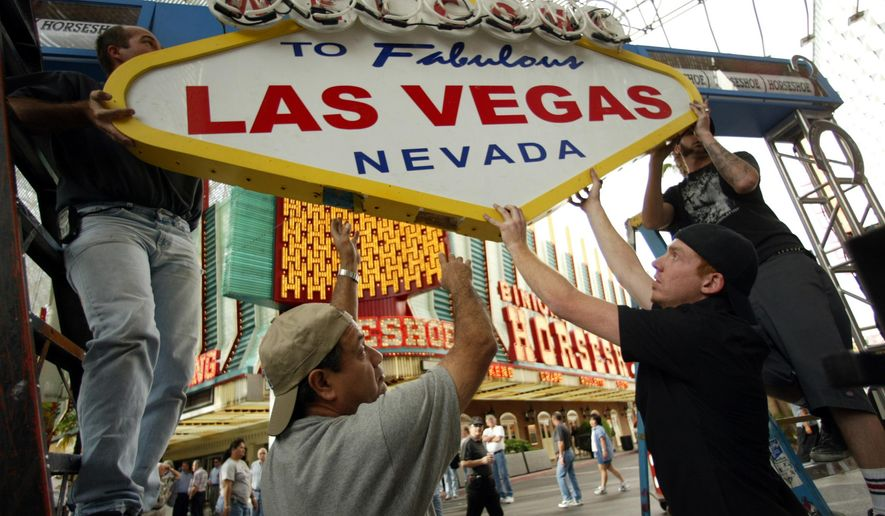 In this April 1, 2004, file photo, workers prepare the stage for a ribbon-cutting ceremony in front of Binion's Horseshoe Casino on Fremont Street in downtown Las Vegas. Forty neon signs that once drew visitors to some of Las Vegas' most iconic casino-hotels and other venues will shine again for the public starting Wednesday, Jan. 31, 2018, night at the Neon Museum. (AP Photo/Joe Cavaretta, File)