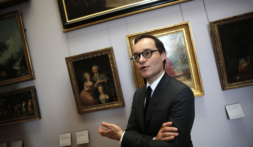 Head of the paintings department at the Louvre museum, Sebastien Allard, answers reporters next to paintings looted by Nazis during World War II, in Paris, Tuesday, Jan. 30, 2018. In a move aimed at returning work of art looted by Nazis during World War II, the Louvre museum has opened two showrooms with 31 paintings on display which can be claimed by their legitimate owners. (AP Photo/Christophe Ena)