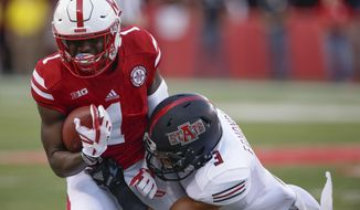 FILE - In this Sept. 2, 2017, file photo, Nebraska wide receiver Tyjon Lindsey (1) is tackled by Arkansas State defensive back B.J. Edmonds (3) during the first half of an NCAA college football game in Lincoln, Neb. Nebraska receiver Tyjon Lindsey and walk-on defensive lineman Dylan Owen were hospitalized after falling ill during winter conditioning drills, coach Scott Frost confirmed to two newspapers Tuesday, Jan. 30, 2018. (AP Photo/Nati Harnik, File)