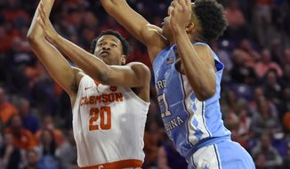 Clemson's Malik William (20) shoots while defended by North Carolina's Sterling Manley during the first half of an NCAA college basketball game Tuesday, Jan. 30, 2018, in Clemson, S.C. (AP Photo/Richard Shiro)