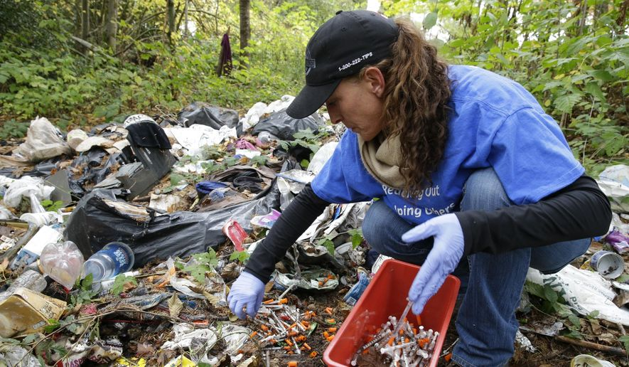 In this Nov. 8, 2017, file photo, Steph Gaspar, a volunteer outreach worker with The Hand Up Project, an addiction and homeless advocacy group, cleans up needles used for drug injection that were found at a homeless encampment in Everett, Wash. The U.S. Centers of Diseases Control and Prevention says 42,000 people died of overdoses in 2016 from opioids, a class of drug that includes powerful prescription painkillers such as OxyContin and Vicodin; illegal heroin; and fentanyl, a strong synthetic drug sold both through prescriptions and on the street. (AP Photo/Ted S. Warren)