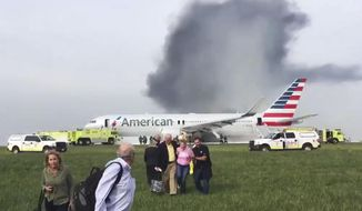 FILE - In this Oct. 28, 2016, file photo provided by passenger Jose Castillo, fellow passengers walk away from a burning American Airlines jet that aborted takeoff and caught fire on the runway at Chicago's O'Hare International Airport. Investigators say communication problems between flight attendants and pilots put evacuating passengers at more risk after the plane caught fire. The National Transportation Safety Board said Tuesday, Jan. 30, 2018, that flight attendants didn't know how to use the intercom system to speak with pilots before they directed passengers to use an emergency exit behind an engine that was still running. (Jose Castillo via AP, File)