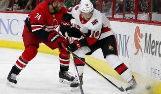 Ottawa Senators' Ryan Dzingel (18) battles with Carolina Hurricanes' Jaccob Slavin (74) during the first period of an NHL hockey game, Tuesday, Jan. 30, 2018, in Raleigh, N.C. (AP Photo/Karl B DeBlaker)