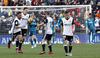 Valencia's Santi Mina, second left, is congratulated by teammate after scoring a goal against Real Madrid during the Spanish La Liga soccer match between Valencia and Real Madrid at the Mestalla stadium in Valencia, Spain, Saturday, Jan. 27, 2018. (AP Photo/Alberto Saiz)