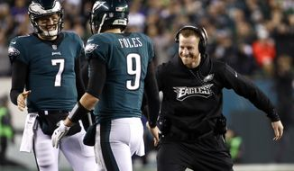 FILE - In this Sunday, Jan. 21, 2018, file photo, Philadelphia Eagles' Carson Wentz, right,  congratulates Nick Foles (9) during the second half of the NFL football NFC championship game against the Minnesota Vikings in Philadelphia. Wentz, who is injured, watched both playoff games from the sideline, rooting hard for his teammates and enjoying their success without him. He'll be their No. 1 fan Sunday when they take on the New England Patriots and try to win the franchise's first NFL title since 1960. (AP Photo/Patrick Semansky, File)