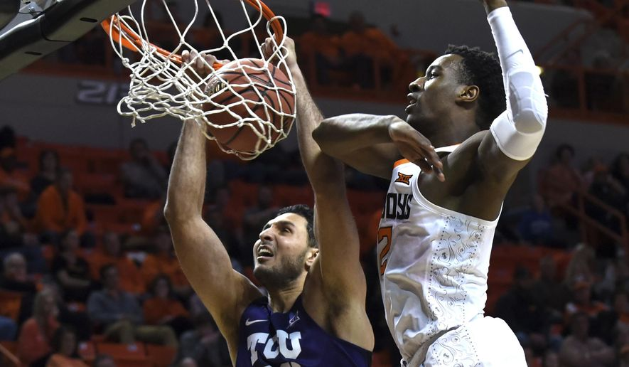 TCU forward Ahmed Hamdy (23) dunks despite pressure from Oklahoma State forward Cameron McGriff in the second half of a NCAA college basketball game in Stillwater, Okla., Tuesday, Jan. 30, 2018. Hamdy scored 9 points in the 79-66 TCU win over Oklahoma State.(AP Photo/Brody Schmidt)
