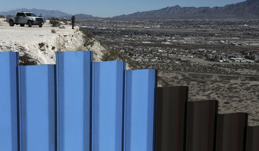In this Jan. 25, 2017, file photo, an agent of the border patrol, observes near the Mexico-US border fence, on the Mexican side, separating the towns of Anapra, Mexico and Sunland Park, N.M.  (AP Photo/Christian Torres, File)