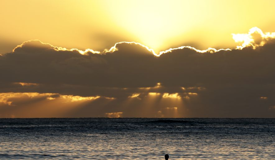 Swimmers watch the sun set behind clouds over the Pacific Ocean seen from Waikiki Beach in Honolulu, Hawaii, Saturday, Dec. 31, 2016, the last sunset of 2016. (AP Photo/Carolyn Kaster)