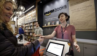 FILE - In this Nov. 3, 2015, file photo, customer Kirsty Carey, left, gets ready to swipe her credit card for clerk Marissa Pacchiarotti, as she makes one of the first purchases at the opening day for Amazon Books in Seattle. Amazon has opened more than a dozen locations of Amazon Books, which also sell some toys, electronics and Amazon gadgets. (AP Photo/Elaine Thompson, File)