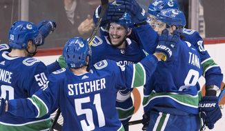 Vancouver Canucks left wing Sven Baertschi, center, celebrates his overtime goal against the Colorado Avalanche during an NHL hockey game Tuesday, Jan. 30, 2018, in Vancouver, British Columbia. The Canucks won 4-3. (Jonathan Hayward/The Canadian Press via AP)