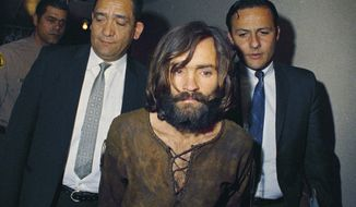 Charles Manson is escorted to his arraignment in 1969 on conspiracy-murder charges in connection with the Sharon Tate murder case. The corpse of Manson will remain in a morgue for at least another month before would-be heirs can argue in court over who gets his remains. A Kern County Superior Court commissioner on Wednesday, Jan. 31, 2018, set a March 7 hearing in the dispute. (AP Photo, File)