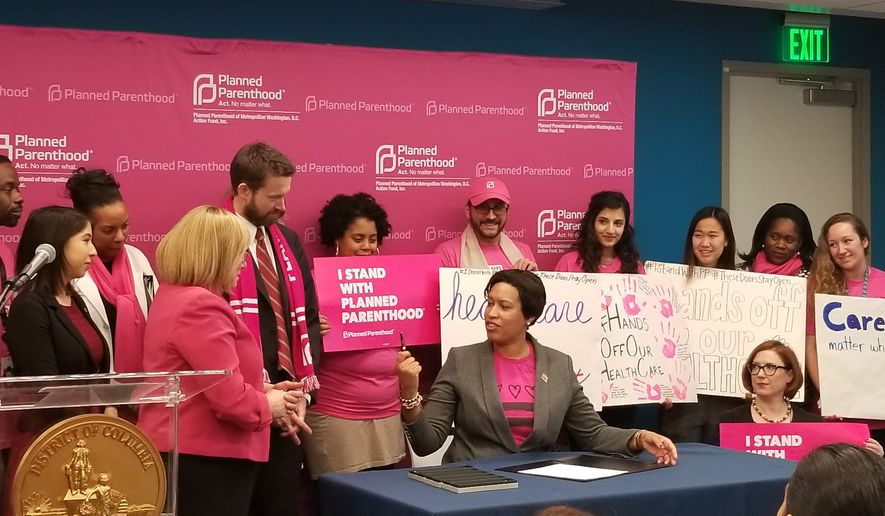 Mayor Muriel Bowser (center), a Democrat, signs a bill written by D.C. council member Charles Allen (left), a Democrat representing Ward 6, preventing insurance companies from charging more for women's health services like cancer screenings or contraceptive costs. The two endorsed the bill together on Wednesday January 31st at Planned Parenthood's Carol Whitehill Moses Center in the Northeast of the city. (Julia Airey / The Washington Times)