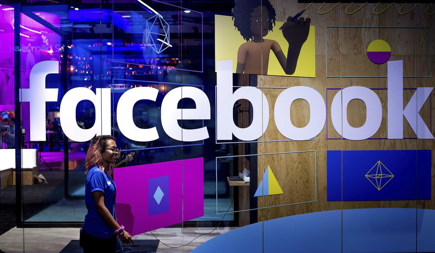 In this Tuesday, April 18, 2017, file photo, a conference worker passes a demo booth at Facebook's annual F8 developer conference, in San Jose, Calif. Facebook Inc. reports earnings Wednesday, Jan. 31, 2018. (AP Photo/Noah Berger, File)