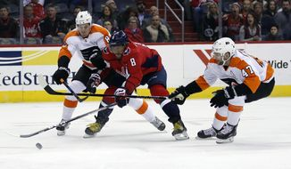 Washington Capitals left wing Alex Ovechkin (8), from Russia, attempts a shot between Philadelphia Flyers defenseman Robert Hagg (8), from Sweden, and defenseman Andrew MacDonald (47) during the first period of an NHL hockey game Wednesday, Jan. 31, 2018, in Washington. (AP Photo/Alex Brandon) ** FILE **
