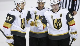 Vegas Golden Knights' David Perron, right, celebrates his goal with teammates Shea Theodore, left, and Pierre-Edouard Bellemare, of France, during the third period of an NHL hockey game against the Calgary Flames in Calgary, Alberta, Tuesday, Jan. 30, 2018. (Jeff McIntosh/The Canadian Press via AP)