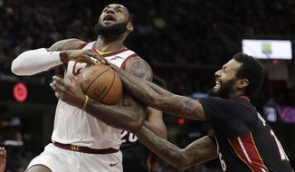 Miami Heat's James Johnson, right, knocks the ball loose from Cleveland Cavaliers' LeBron James in the first half of an NBA basketball game, Wednesday, Jan. 31, 2018, in Cleveland. (AP Photo/Tony Dejak)