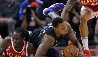 Charlotte Hornets guard Treveon Graham (21) and Atlanta Hawks forward Taurean Prince (12) dive for a loose ball during the first half of an NBA basketball game Wednesday, Jan. 31, 2018, in Atlanta. (AP Photo/John Bazemore)