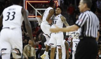 Cincinnati's Jacob Evans (1) celebrates with Jarron Cumberland (34) after scoring in the final second of the first half of the teams NCAA college basketball game against Houston, Wednesday, Jan. 31, 2018, in Highland Heights, Ky. (AP Photo/John Minchillo)