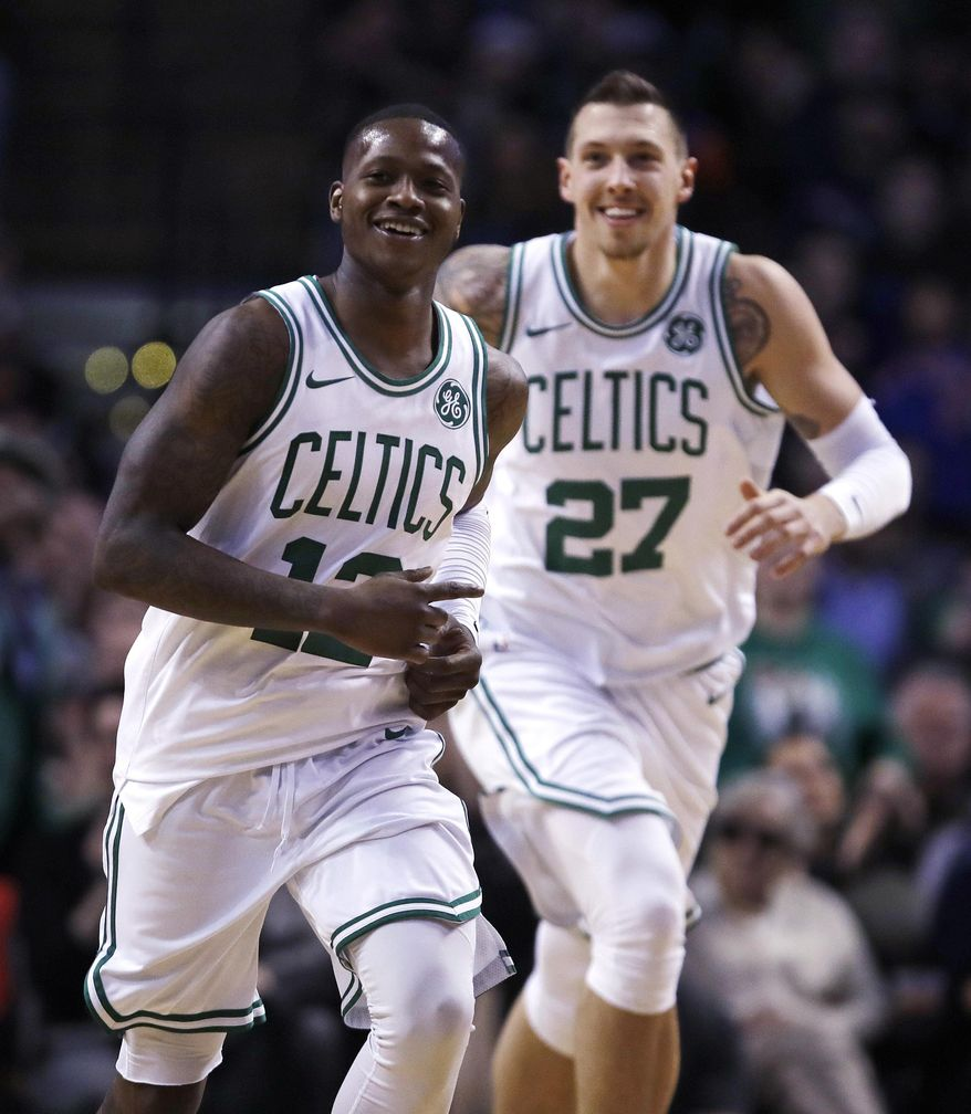 Boston Celtics guard Terry Rozier (12) smiles as he heads up court with forward Daniel Theis, after completing a triple-double with a pass to Theis for a slam dunk, during the second half of an NBA basketball game in Boston, Wednesday, Jan. 31, 2018. Rozier filled in nicely for the injured Kyrie Irving, logging his first career triple-double with 17 points, 11 rebounds and 10 assists in his first NBA start. The Celtics won 103-73. (AP Photo/Charles Krupa)