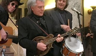 Country singer Marty Stuart, center, performs at the Mississippi Capitol in Jackson on Wednesday, Jan. 31, 2018. Also shown are two members of his band, The Fabulous Superlatives. Harry Stinson is behind Stuart and Chris Scruggs is on the right. Stuart says he is planning to develop a museum called Marty Stuart's Congress of Country Music in his hometown of Philadelphia, Miss.( AP Photo/Emily Wagster Pettus)