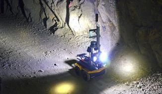A robot rolls through an underground mine at the Edgar Mine set of Denver, Colo., Dec. 13, 2017. The U.S. Environmental Protection Agency is considering robots and other technologies to investigate abandoned or inactive mines to learn what needs to be done with contaminated water spilling out of the mines and into rivers. Many of the mines are poorly understood and dangerous because of bad air and cave-ins. (AP Photo/Tatiana Flowers)