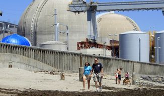 FILE - In this June 30, 2011 file photo, people walk on the sand near the shuttered San Onofre nuclear power plant in San Clemente, Calif. The Southern California utility that oversaw a nuclear plant that was shut down has reached a settlement with attorneys representing consumers who felt they were footing too much of the bill for the closure. The settlement announced Tuesday night, Jan. 30, 2018, by Southern California Edison saves its customers $775 million through early 2022. (AP Photo/Lenny Ignelzi, File)
