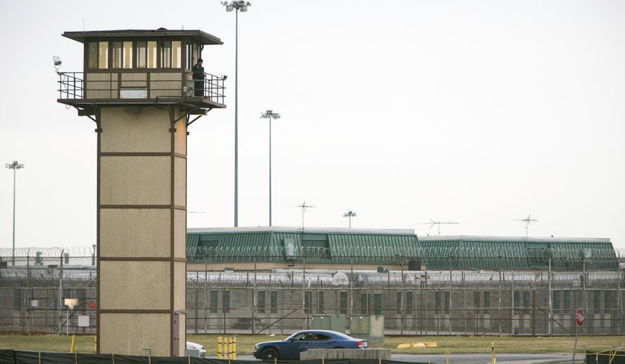 FILE - In this Feb. 1, 2017, file photo, a prison guard stands on a tower during a hostage situation at James T. Vaughn Correctional Center in Smyrna, Del. An independent review ordered by Delaware Gov. John Carney after the riot at Vaughn Correctional Center includes scores of recommendations for reforms. But officials say many of those reforms depend on adequate staffing, which remains an elusive goal. (Suchat Pederson/The News Journal via AP)