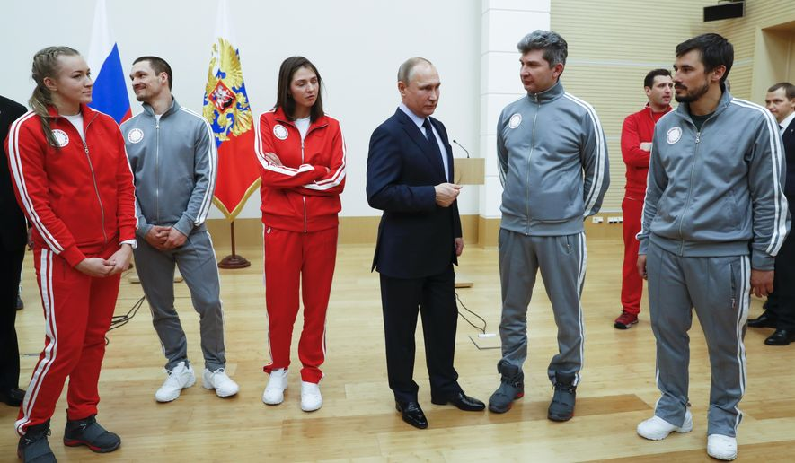 """Russian President Vladimir Putin, center, poses for a photo with Russian athletes who will take part in the upcoming 2018 Pyeongchang Winter Olympic Games in South Korea, at the Novo-Ogaryovo residence outside in Moscow, Russia, Wednesday, Jan. 31, 2018. As punishment for what it deemed a doping scheme during the 2014 Sochi Olympics, the International Olympic Committee has invited 169 Russians to compete under a neutral flag using the name """"Olympic Athletes from Russia."""" (Grigory Dukor/Pool Photo via AP)"""