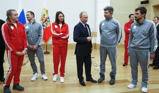 "Russian President Vladimir Putin, center, poses for a photo with Russian athletes who will take part in the upcoming 2018 Pyeongchang Winter Olympic Games in South Korea, at the Novo-Ogaryovo residence outside in Moscow, Russia, Wednesday, Jan. 31, 2018. As punishment for what it deemed a doping scheme during the 2014 Sochi Olympics, the International Olympic Committee has invited 169 Russians to compete under a neutral flag using the name ""Olympic Athletes from Russia."" (Grigory Dukor/Pool Photo via AP)"