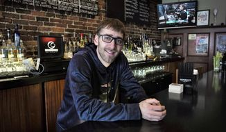 In this Sunday, Jan. 28, 2018, photo, Jeff John, of Boston, general manager of Common Ground Bar and Grill, stands for a photograph at the restaurant, in Boston. When customers watch the Super Bowl at Common Ground Bar and Grill on Sunday, waiters and bartenders will be pausing now and then to watch, as well. John may need to remind them to work, but he also understands his staff wants to see if the New England Patriots will win their third NFL title in four years. (AP Photo/Steven Senne)