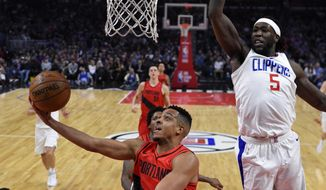 Portland Trail Blazers guard CJ McCollum, left, shoots as Los Angeles Clippers forward Montrezl Harrell, right, defends during the first half of an NBA basketball game, Tuesday, Jan. 30, 2018, in Los Angeles. (AP Photo/Mark J. Terrill)