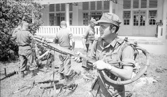 """In this 1965 photo, AP correspondent Peter Arnett holds a captured Chinese flamethrower, in Vietnam. As the country celebrated Lunar New Year after midnight on Jan. 31, 1968, communist forces launched a wave of surprise attacks that became known as the Tet Offensive and would change the course of the Vietnam War. The AP's Peter Arnett reported on the Vietnam War from 1962 until its end in 1975. On the 50th anniversary of the Tet Offensive, the AP is publishing this edited extract from his book """"We're Taking Fire: A Reporter's View of the Vietnam War, Tet and the Fall of LBJ."""" (AP Photo)"""