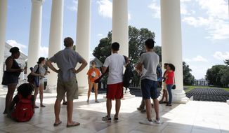 In this Aug. 18, 2017 file photo, first year students tour the University of Virginia in Charlottesville, Va., a week after a white nationalist rally took place on campus. A group that monitors extremism in the U.S. says white supremacists brought their messages to college campuses in a surging number of cases last school year. (AP Photo/Jacquelyn Martin)