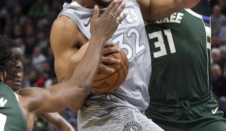 Minnesota Timberwolves' Karl-Anthony Towns, left, tries to drive past Milwaukee Bucks' John Henson in the first half of an NBA basketball game Thursday, Feb. 1, 2018, in Minneapolis. (AP Photo/Jim Mone)