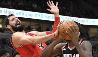FILE- In this Jan. 1, 2018, file photo, Chicago Bulls forward Nikola Mirotic, left, defends against Portland Trail Blazers forward Al-Farouq Aminu (8) during the second half of an NBA basketball game in Chicago. A person familiar with the decision says the New Orleans Pelicans have acquired forward Nikola Mirotic and a second-round draft pick from the Chicago Bulls for center Omer Asik, guards Jameer Nelson and Tony Allen, and a future first-round pick. The person spoke to The Associated Press on condition of anonymity Thursday, Feb. 1, 2018,  because neither team has announced the trade. (AP Photo/David Banks, File) **FILE**