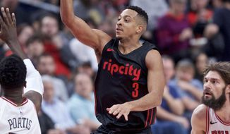 Portland Trail Blazers guard CJ McCollum shoots between Chicago Bulls forward Bobby Portis, left, and center Robin Lopez during the second half of an NBA basketball game in Portland, Ore., Wednesday, Jan. 31, 2018. (AP Photo/Craig Mitchelldyer)