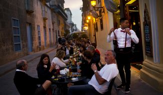 A waiter serves customers at a private restaurant's outdoor seating in Havana, Cuba, Wednesday, Jan. 31, 2018. Eight years after Cuba's President Raul Castro widened the niche for private enterprise in Cuba's state-dominated economy, he has thrown the brakes on, raising fundamental questions about the nation's economic path. (AP Photo/Ramon Espinosa)