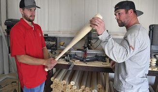 In this Jan. 26, 2018 photo, Leland Wetzel, left, and Ross Harrison inspect a freshly-turned baseball bat produced on a computer controlled lathe at their shop in Dean, Texas. Wetzel owns Xylo Bats and has begun producing bats for Major League Baseball. (Torin Halsey/Wichita Falls Times Record News via AP)