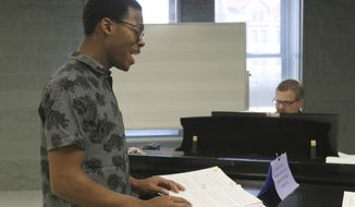 """In this Jan. 17, 2018 photo, student Darius Lee, left, goes through a song with artist-in- residence Kevin Long during the New Musicals Workshop Immersion class at Millikin University in Decatur, Ill. Tysen writes dialogue and lyrics, and Chris Miller writes music. The two New Yorkers, authors of the Broadway musical """"Tuck Everlasting,"""" visited Millikin from Jan. 3 to 21, 2018, during the university's immersion term to work with students in fine-tuning their version of """"Eric Hermannson's Soul. (Jim Bolwing/Herald & Review via AP)"""