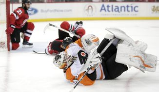 Philadelphia Flyers goalie Alex Lyon, front, rolls on his back after colliding with New Jersey Devils right wing Kyle Palmieri (21) and left wing Miles Wood (44) during the second period of an NHL hockey game, Thursday, Feb. 1, 2018, in Newark, N.J. (AP Photo/Julio Cortez)
