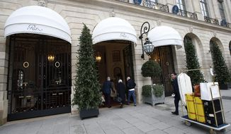 FILE - In this Jan.11, 2018 file photo, people enter the Ritz hotel in Paris, Thursday, Jan. 11, 2018. The Ritz hotel is putting to auction more than 10,000 pieces of furniture and decorative objects including bathtubs, beds and minibars emblematic of the luxury afforded by the wealthy clients of the glitzy palace. (AP Photo/Michel Euler, File)