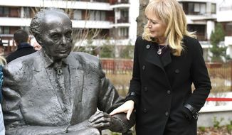 One of the daughters of the politician Katrina Lantos Swett touches the statue of her father, late US Congressman of Hungarian origin Tom Lantos during the unveiling ceremony near Lantos' former school, Berzsenyi Daniel Secondary School, in Tom Lantos Walk in Budapest, Hungary, Thursday, Feb. 1, 2018. (Noemi Bruzak/MTI via AP)