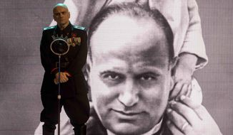 "In this photo taken during the filming of the movie ""I'm Back"", actor Massimo Popolizio, who plays the part of Benito Mussolini, stands in front of a giant image of the late dictator. A new film opening in Italy proposes the once-unthinkable return of dictator Benito Mussolini to current-day Italy, smack in the middle of an election campaign dominated by populist and neo-fascist sentiments. ""I'm Back,"" is the Italian riff on the 2015 German film ""Look Who's Back,"" which hypothesized a modern-day resurrection for Adolf Hitler. (Claudio Iannone via AP Photo)"