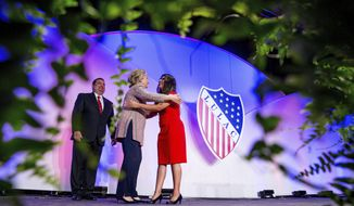 FILE - In this July 14, 2016 photo Democratic presidential candidate Hillary Clinton, accompanied by LULAC President Roger C. Rocha, Jr., left, hugs University of Texas student Dreamer Lizeth Urdiales, right, as she arrives to speaks at the 87th League of United Latin American Citizens National Convention at the Washington Hilton in Washington. Rocha, Jr. the president of the oldest Latino civil rights organization in the U.S. is facing harsh criticism for endorsing President Donald Trump's immigration framework that includes a border wall. (AP Photo/Andrew Harnik,File)