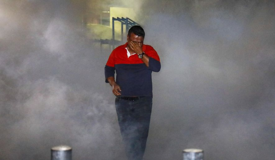 A Maldivian opposition protestor demanding the release of political prisoners engulfed in tear gas fired by police during a protest in Male, Maldives, Friday, Feb. 2, 2018. Political opponents of the Maldives government clashed with police on the streets of the capital early Friday after the Supreme Court ordered the release of imprisoned politicians, including an ex-president living in exile in Britain.(AP Photo/Mohamed Sharuhaan)