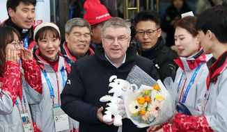 International Olympic Committee President Thomas Bach, center, poses for photographers while being greeted by the 2018 Pyeongchang Winter Olympic volunteers upon his arrival at Jinbu Station in Pyeongchang, Tuesday, Jan. 30, 2018. South Korea on Tuesday expressed regret over North Korea's cancellation of one of the joint cooperation projects planned for next month's Winter Olympics, a development highlighting the delicate nature of ties between the rivals split for seven decades. (Lim Byung-shick/Yonhap via AP)
